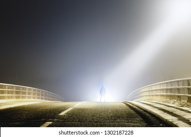 A sinister hooded figure silhouetted by a light beam from a UFO on a spooky misty road at night.