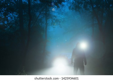 A sinister hooded figure standing in front of a car headlights on a spooky forest road on a misty evening.