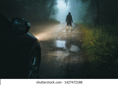 A sinister hooded figure standing in front of car headlights. On a spooky muddy forest road at night.