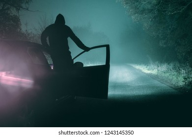 A sinister hooded figure standing on a car silhouetted on a foggy winters night. With a cold, grainy muted edit.