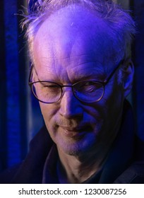 Sinister looking middle age man being illuminated with a blue light.