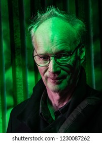 Sinister looking middle age man being illuminated with a green light.