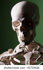 Sinister looking skull and shoulders of a skeleton emerging from the shadows against a green background