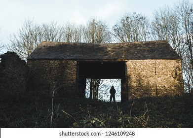 A sinister, silhouetted, hooded figure stands in a ruined old barn on a winters day. With a cold muted edit.