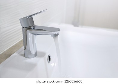 Sink with a chrome tap from which a stream of water flows, white washbasin. Image