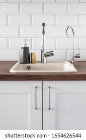 Schlink mit Wasserhahn in der Küche. Lärmbelästigung, Wassereinsparung, Geschirrspülungen in heller skandinavischer Innenansicht