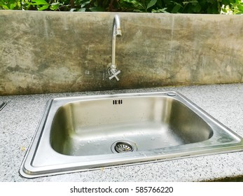 Sink and faucet at outdoor kitchen in backyard garden.