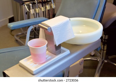 Sink for patient in dental care clinic showing chair in background