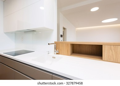 Sink with tap and induction cooker on white worktop of contemporary kitchen