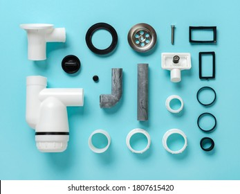 Sink waste water trap parts knolled on a blue background. Knolling style composition of new plastic sink drain with stainless steel strainer. Install, clean and repair of domestic plumbing fixtures.