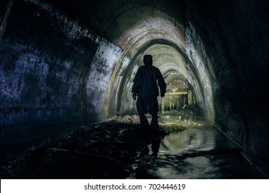 Sinker tunnel worker in protective suite in underground gassy sewer tunnel