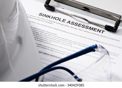 Sinkhole assessment form with safety glasses and hardhat on clipboard