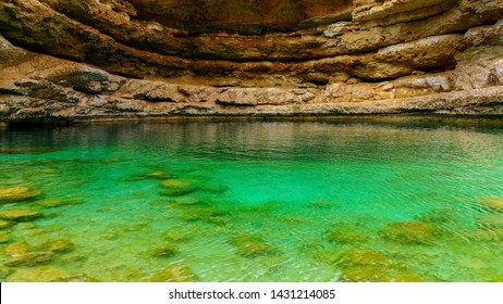 Sinkhole Oman. Green water in a natural pool created by sea water.