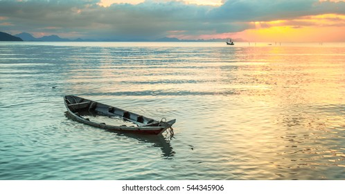 Sinking boat at sea against the evening sunset.