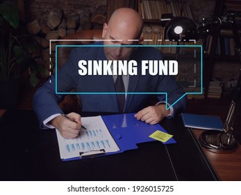 SINKING FUND text in block of quotes. Budget analyst doing paperwork Asinking fundis a fund containing money set aside or saved to pay off a debt or bond.