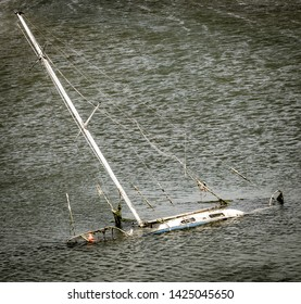 Sinking sunken sailing boat in rough water