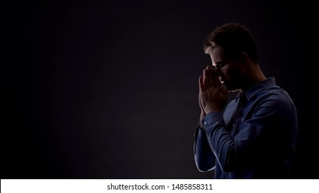 Sinner praying to God in dark room, asking for forgiveness, confession concept