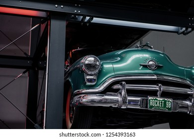 SINSHEIM, GERMANY - OCTOBER 16, 2018: Technik Museum. Green shiny retro car on the special high stand at auto show.
