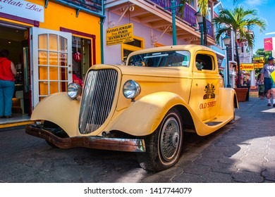 Sint Maarten / Caribbean / Netherlands - January 23.2008: View on the yellow vintage car parked on the street with colorful buildings and palm trees in the background during the sunny day.