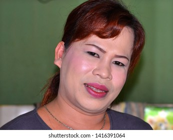 SINTANG, KALIMANTAN / INDONESIA - SEP 28, 2013: Young genderqueer hairdresser with lipstick and thick, skin-whitening make-up poses for the camera, on Sep 28, 2013.