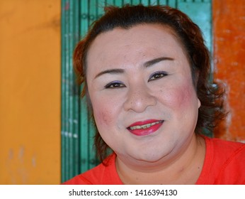 SINTANG, KALIMANTAN / INDONESIA - SEP 28, 2013: Chubby genderqueer hairdresser with lipstick and thick, skin-whitening make-up poses for the camera, on Sep 28, 2013.