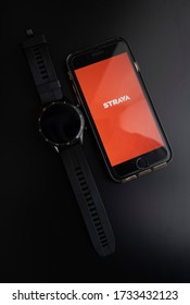 Sint-Niklaas, Belgium - 05 15 2020: Strava application open on a cellphone next two a sport & smartwatch of Huawei on a black background