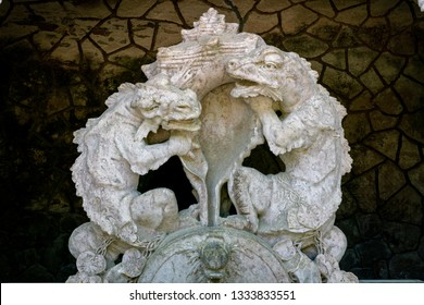 Sintra, Lisbon / Portugal - May 18, 2018: The fountain statues of the lizzard dragons at the portal of the Guardians, the entrance way to the Initiation well in Quinta da Regaleira
