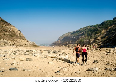 SINTRA, PORTUGAL - CIRCA 2017: A couple doing a hike In Praia da Samarra, a remote beach on Sintra (Lisbon), an activity promoted and organized by an amateur organization.