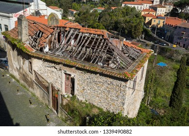SINTRA, PORTUGAL - FEBRUARY 11, 2019: Photo old dilapidated building with a broken red ceramic roof requiring major repairs.