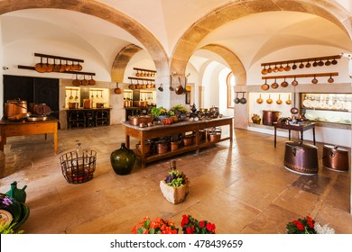 SINTRA, PORTUGAL - JULY 12, 2015: Old country style kitchen with fireplace and copper pans in bright colors with arches. Interior.
