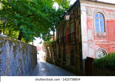 SINTRA, PORTUGAL - JULY 15, 2014: Trees shade a narrow street near the Pena Palace on July 15, 2014 in Sintra, Portugal. Sintra is a popular resort town near Lisbon.