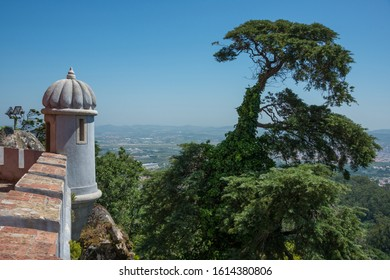 Sintra, Portugal - May 23, 2017: Walls and watchtower of the Pena National Palace and view of the surrounding forest landscape