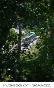 Sintra, Portugal - May 23, 2017: Scene with a bus framed among the foreground of blurry trees going up the hill of Pena Palace