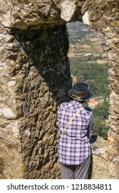 Sintra, Portugal, September 10, 2018: Female torist looking out from the Castle of the Moors to Sintra neighborhood, Portugal