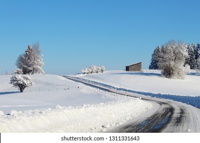 Sinuous country road in beautiful snowy, hilly winter landscape, Allgäu, Bavaria