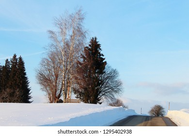 Sinuous country road up to an hill in a beautiful snowy winter landscape, Allgäu, Bavaria