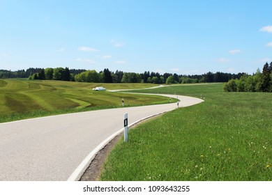 Sinuous country road in the hilly Alpine Upland in spring, blue sky above, Allgäu, Bavaria