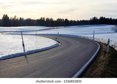 Sinuous country road trough a snowy winter landscape, Allgäu, Bavaria