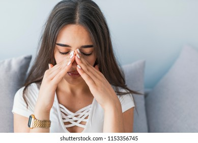 Sinus ache causing very paintful headache. Unhealthy woman in pain. Sharp strong sore. Sinus pain, sinus pressure, sinusitis. Sad woman holding her nose and head because sinus pain