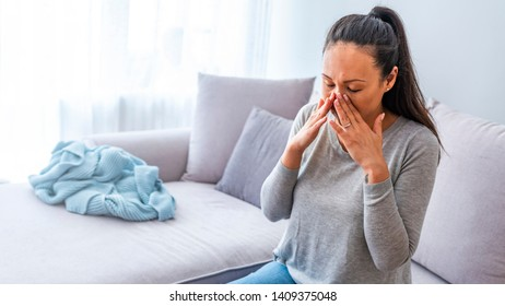Sinus ache causing very paintful headache. Unhealthy Asian woman in pain. Sharp strong sore. Sinus pain, sinus pressure, sinusitis. Sad woman holding her nose and head because sinus pain