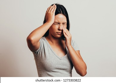 Sinus pain, sinus pressure, sinusitis. Sad woman holding her nose and head because sinus pain