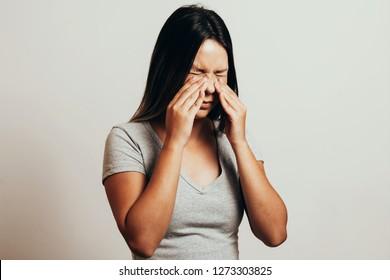 Sinus pain, sinus pressure, sinusitis. Sad woman holding her nose and head because sinus pain