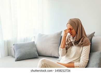Sinus pain, sinus pressure, sinusitis. Sad Muslim woman holding her nose and head because sinus pain. Sinus ache causing very paintful headache. Unhealthy woman in pain. Sharp strong sore