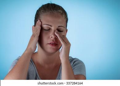 Sinus pain, sinus pressure, sinusitis. Sad woman holding her nose because sinus pain