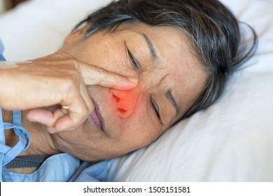 Sinus,Sinusitis, or rhinosinusitis concept. Asia eldery woman suffer from nose congestion, thick nasal mucus, and face pain symptoms from flu and cold.