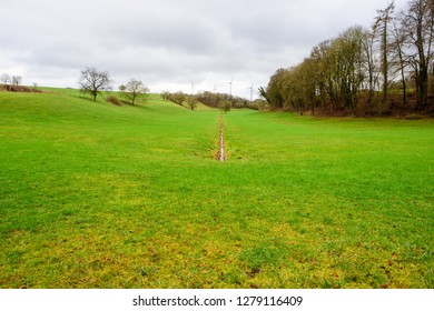 Sinz, Perl, Saarland, Germany - January 8, 2019: An irrigation ditch in a grassy farm field points to wind turbines on the horizon