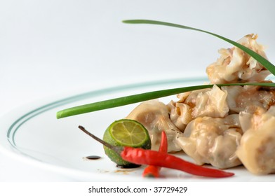 """""""siomai"""" a chinese dumpling made of ground pork topped with leaks and chili"""