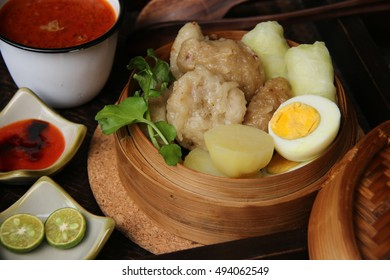 Siomay Bandung. Fish cake dumplings with potato, egg, and cabbage roll in bamboo basket. Served with peanut, chili, sweet soy sauces and lime.