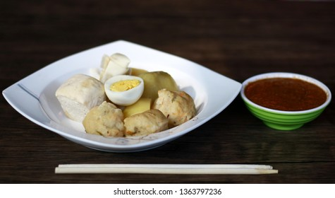 Siomay (fish cake dumplings) and peanut sauce on wood background.