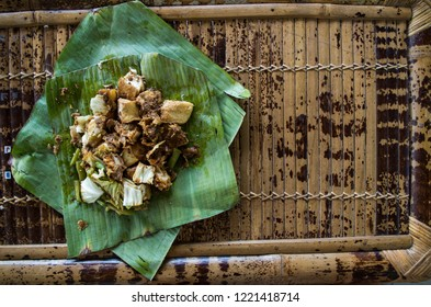 Siomay - Indonesian dish with steamed fish dumpling and vegetables served in peanut sauce in banana leaf - copy space right.